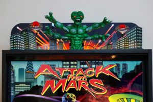 Doug Watson, the creator of the original Attack from Mars art package, was commissioned to design the new topper. Watson hand sculpted the Martian from which the molds were created to produce the new roto-molded animated Martian. Watson also created the other printed topper elements.